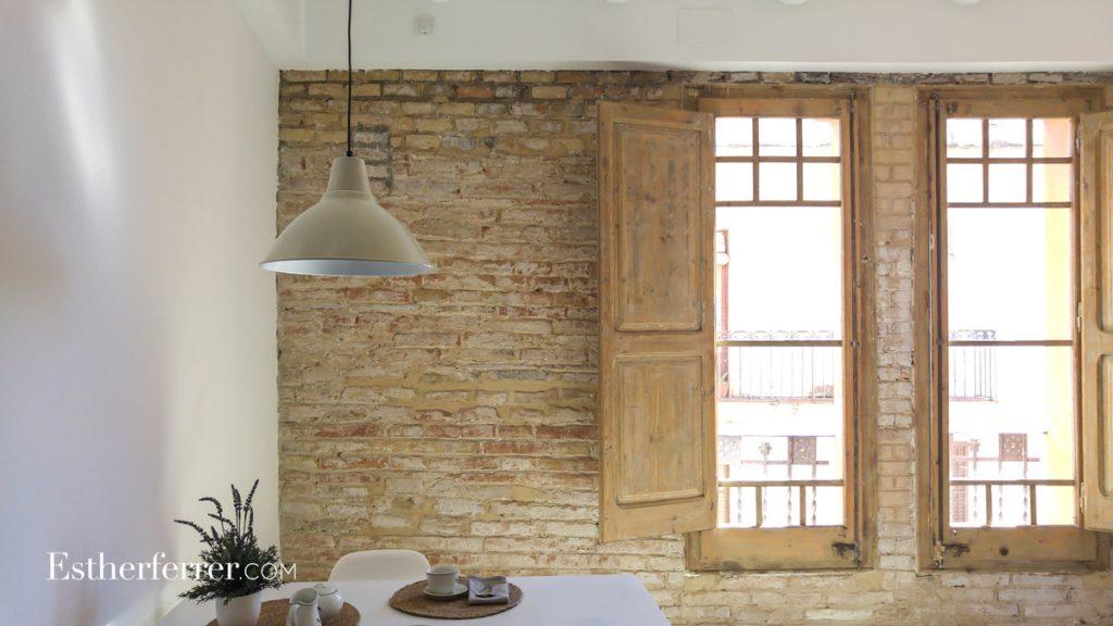 cómo reformar un piso modernista en barcelona sin estropearlo: pared de ladrillo repicada y ventanas de madera decapadas